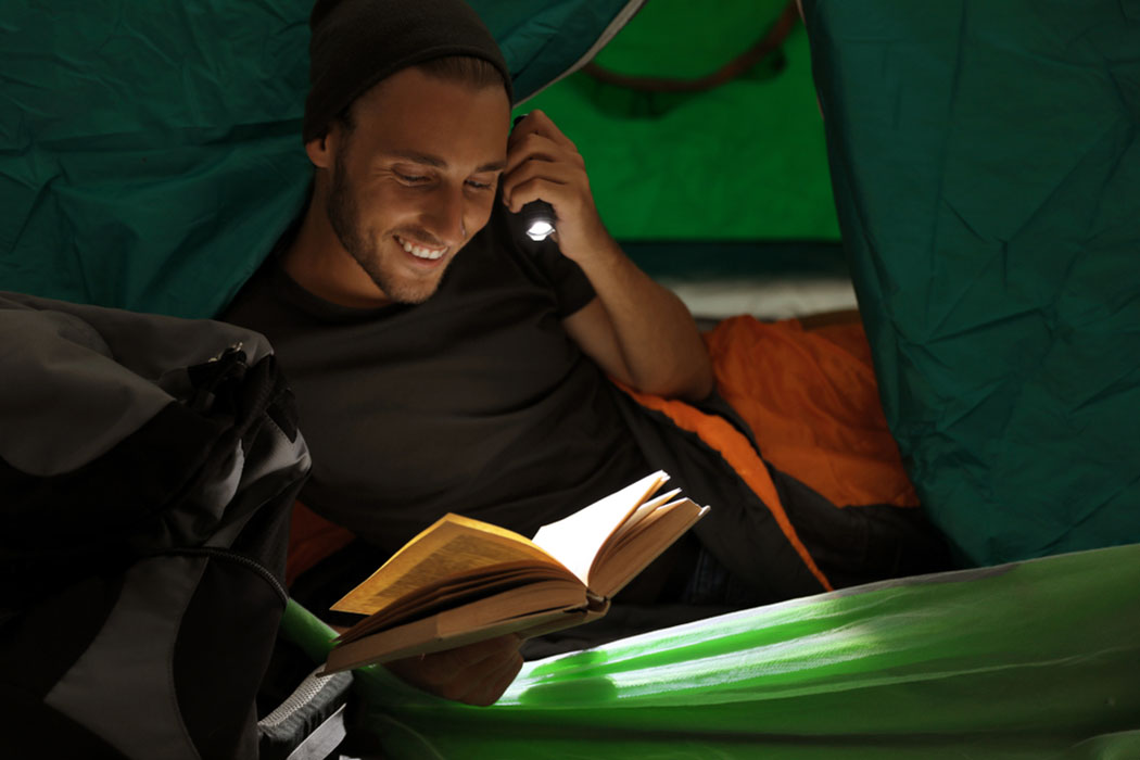 young man in a sleeping bag reading a book